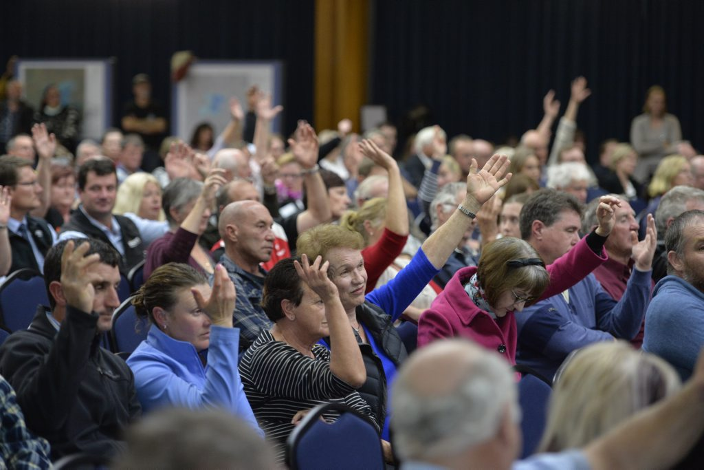Oakey residents raise their hands when asked if they had suffered adverse health effects amid the contamination issue during a meeting with Shine Lawyers ambassador and activist Erin Brockovich.