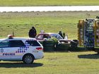 Police and fire fighters attend the scene where a man was killed in a single vehicle accident at Queensland Raceway.