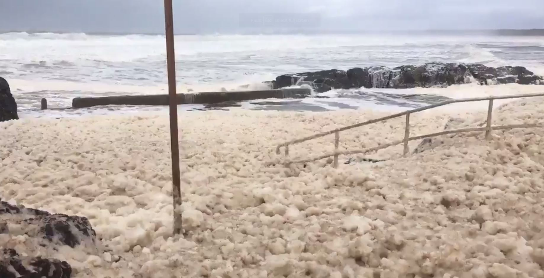 Sawtell Rock Pool is carpeted with foam after wild seas erupted from last night's east coast low.