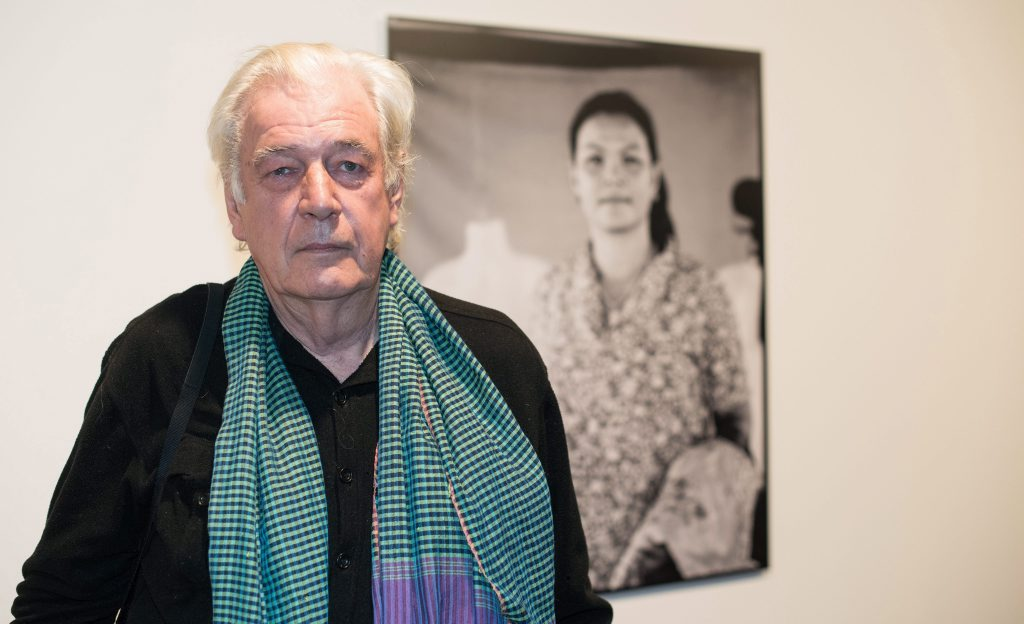 epa04578476 Australian photographer Tim Page, poses in front of his works photographs displayed in the exhibition 'Die Roten Khmer und die Folgen' (lit. The Khmer Rouge and aftermath) after a press conference at the Academy of Arts inBerlin,Germany, 23 January 2015. The exhibition runs from 25 January to 01 March. EPA/BERNDVONJUTRCZENKA