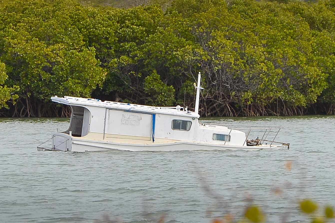 Police search for owner of this boat sinking in the Calliope River.