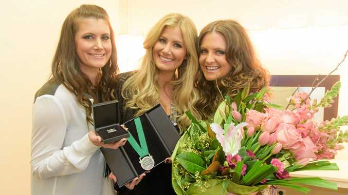 BACK HOME: The McClymonts Mollie, Sam and Brooke with their medals and flowers after they were named as Clarence Valley Ambassadors for 2016 at their 10 Years of Hits show at the Saraton Theatre.