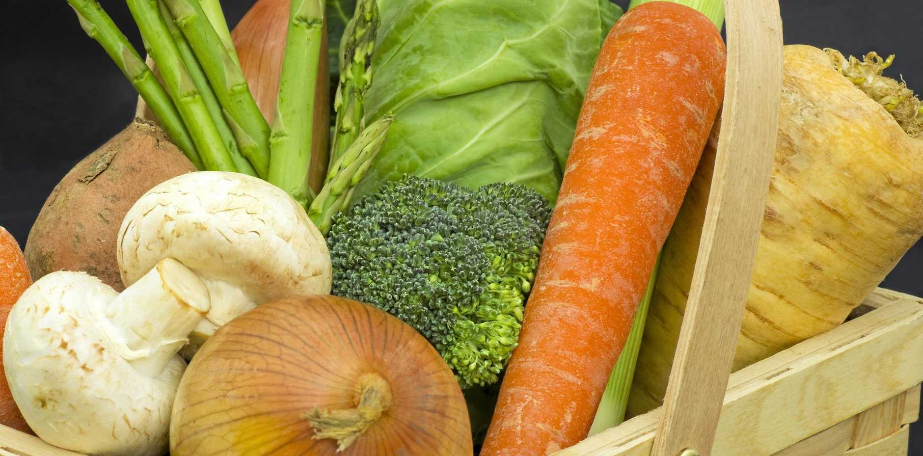 A wooden trug of freshly harvested vegetables, promoting healthy eating and living.