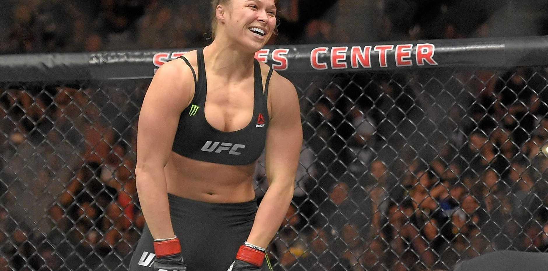 BIG NAME: Ronda Rousey, top, celebrates as Cat Zingano kneels on the mat during a UFC 184 mixed martial arts bantamweight title bout.