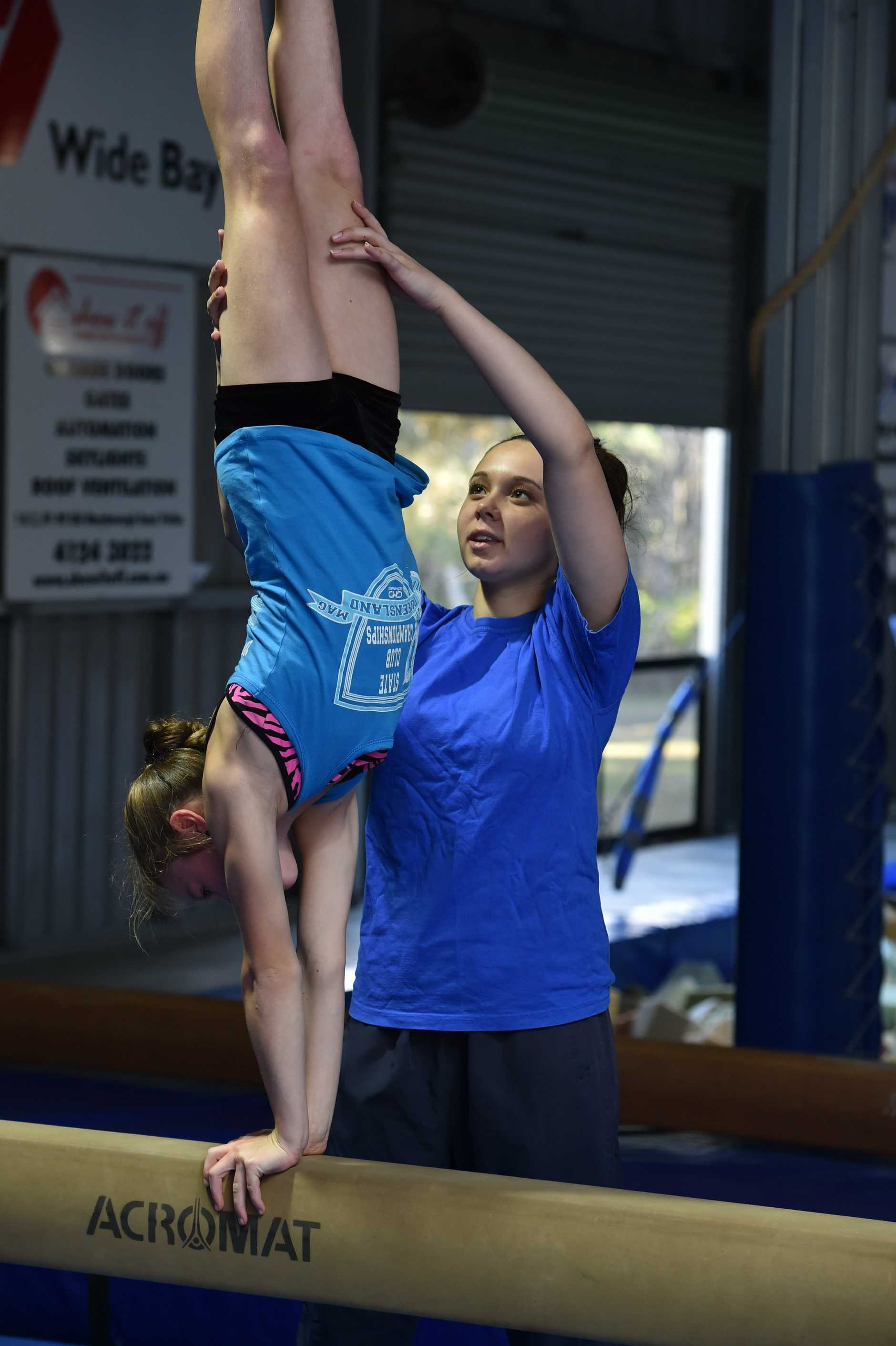 Wide Bay Gymnastics Club - trainer Maddison Beel working with Mia Wright.