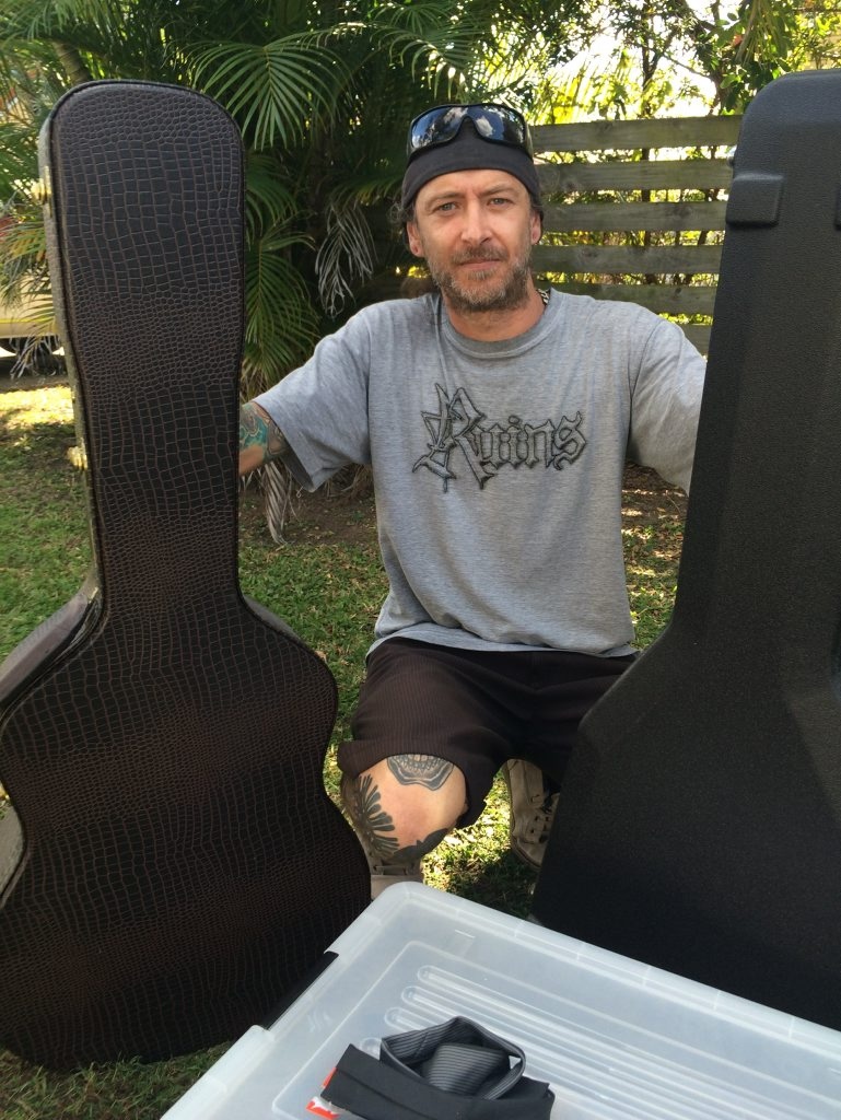 Mt Coolum resident Evan Kelly holds guitars which his friend was able to save from his townhouse. His home was a part of the same building where another townhouse was destroyed by fire.