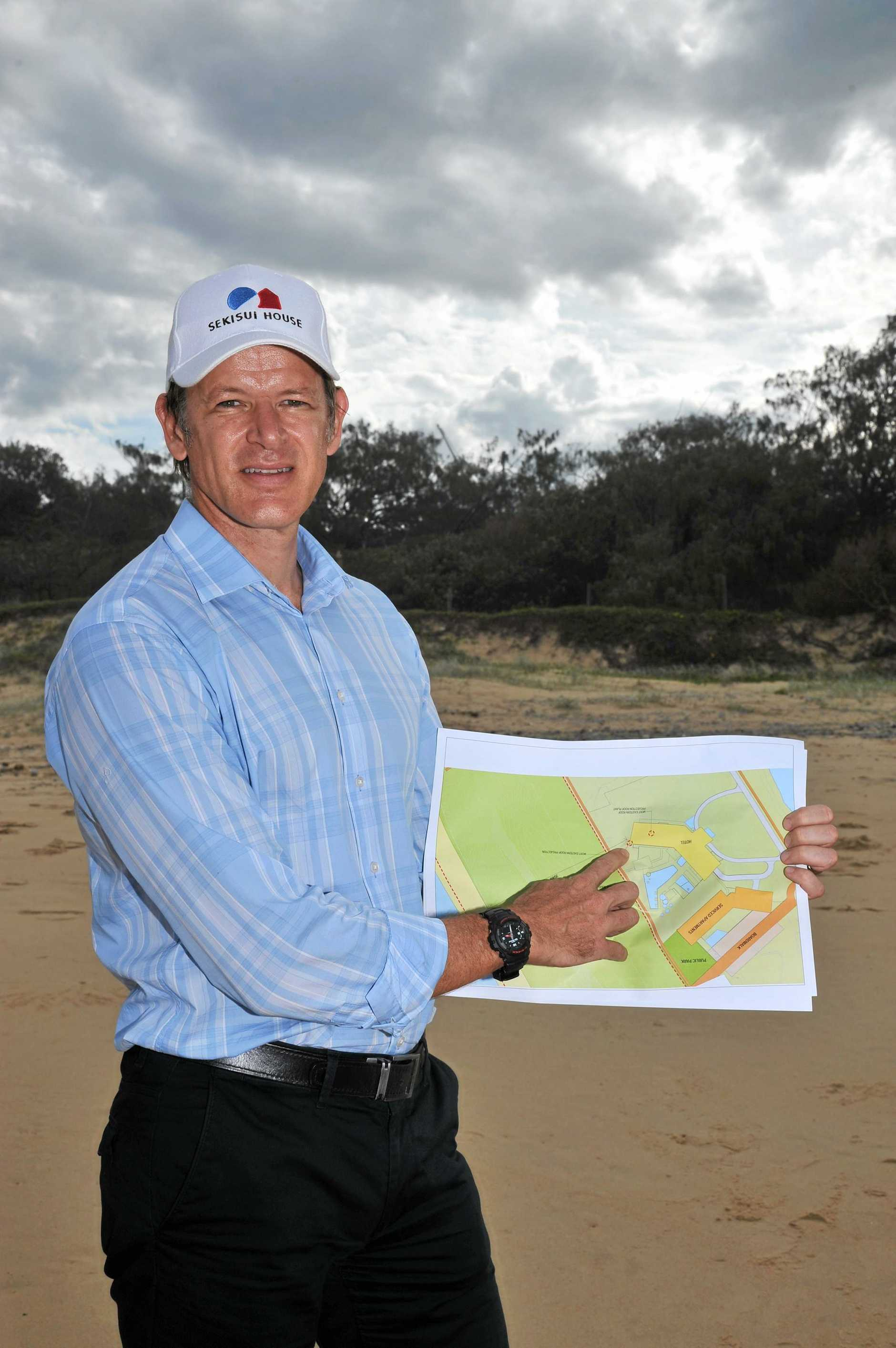 Sekisui erect cranes to show building height of the tallest proposed building plus the position of the front building. Sekisui House Senior Development Manager, Evan Aldridge on Yaroomba beach with cranes behind him.    Photo Greg Miller / Sunshine Coast Daily