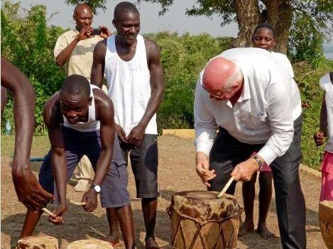 Mountain Blue Farms founder Ridley Bell playing traditional drums in northern Uganda.