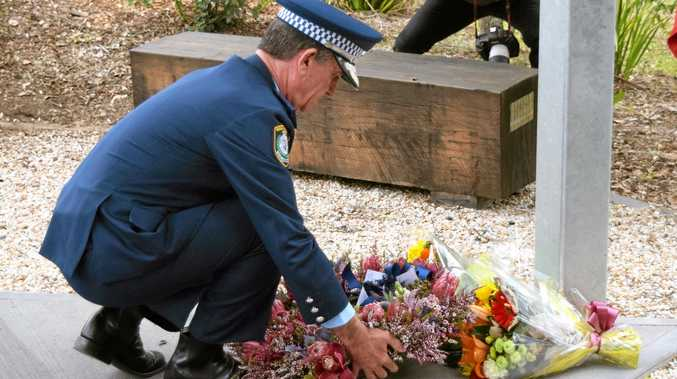 NSW Police Commissioner Andrew Scipione lays flowers at the memorial site for the three Bowraville victims.