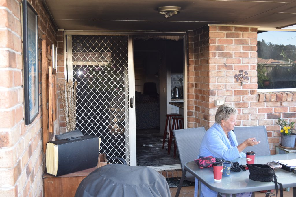 Maroochydore resident Lois Schlipalius speaks with a fire investigator after her unit was severely damaged by fire and smoke.