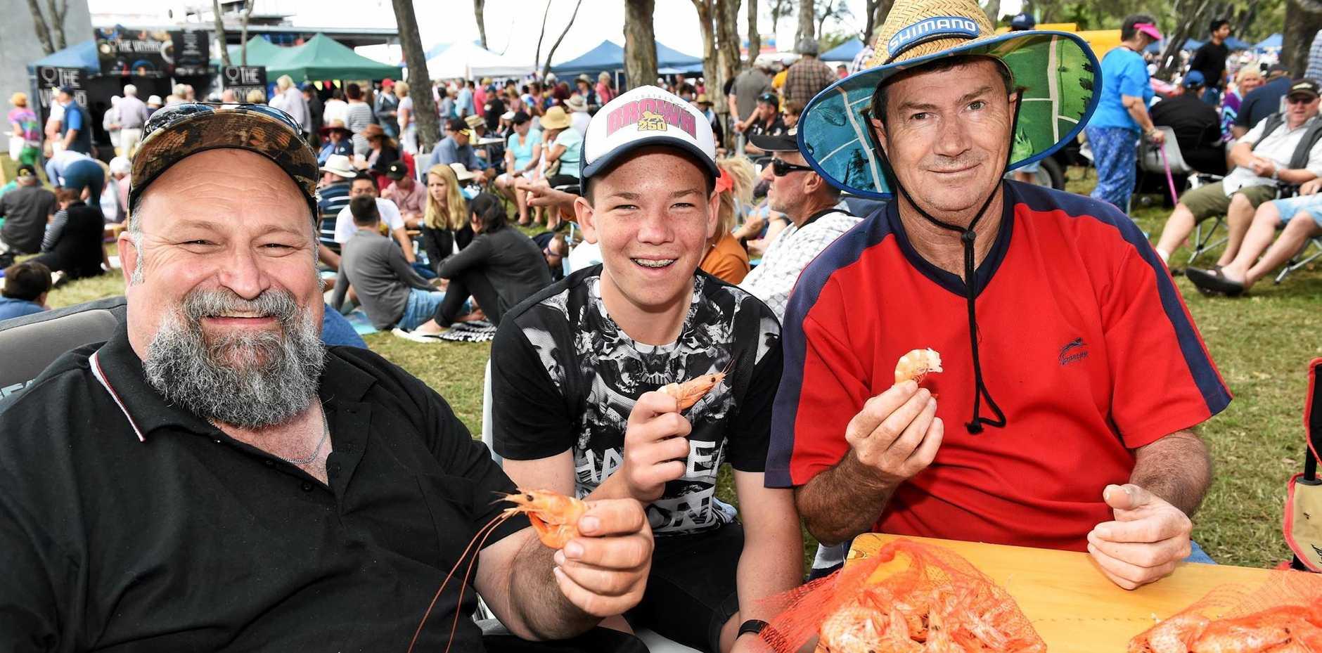 PRAWN CRACKER: Joe Roberts, Sam Hutson and Glen Grenham kept it simple with a bag of prawns each at the Ocean Festival in Urangan yesterday.