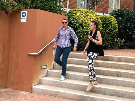 Mrs Douglas (left) leaves Gladstone Courthouse after her husband and sons were charged with arson and robbery offences.