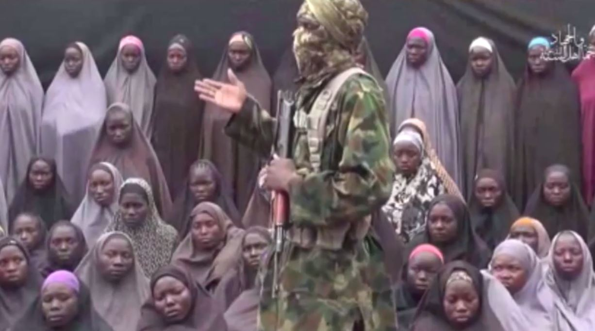 A Boko Haram militant stands in front of a group of young women -- thought to be those kidnapped from Chinok in 2014 -- while calling for its captured fighters to be released.