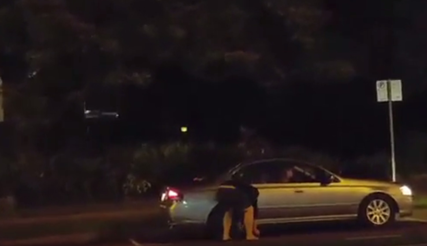 A still from the video showing a man pouring fuel on the back tyre.