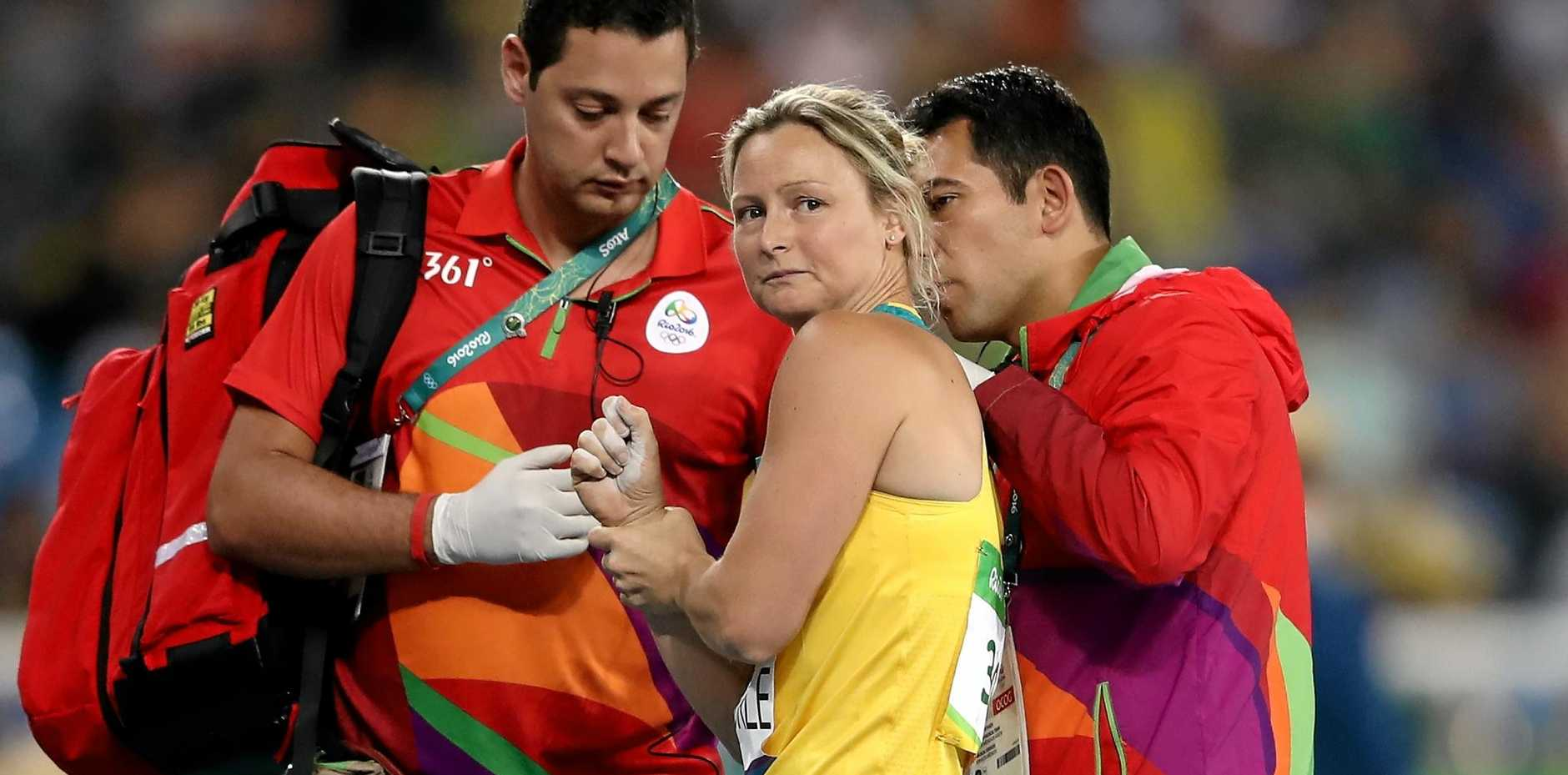 Kim Mickle of Australia is assisted by medical staff after being injured during the women's javelin throw qualifying round.