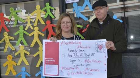 Louise Noble and Rev Dr Johnathan Inkpin deliver an envelope full of messages written by Toowoomba residents to Groom MP John McVeigh's office.