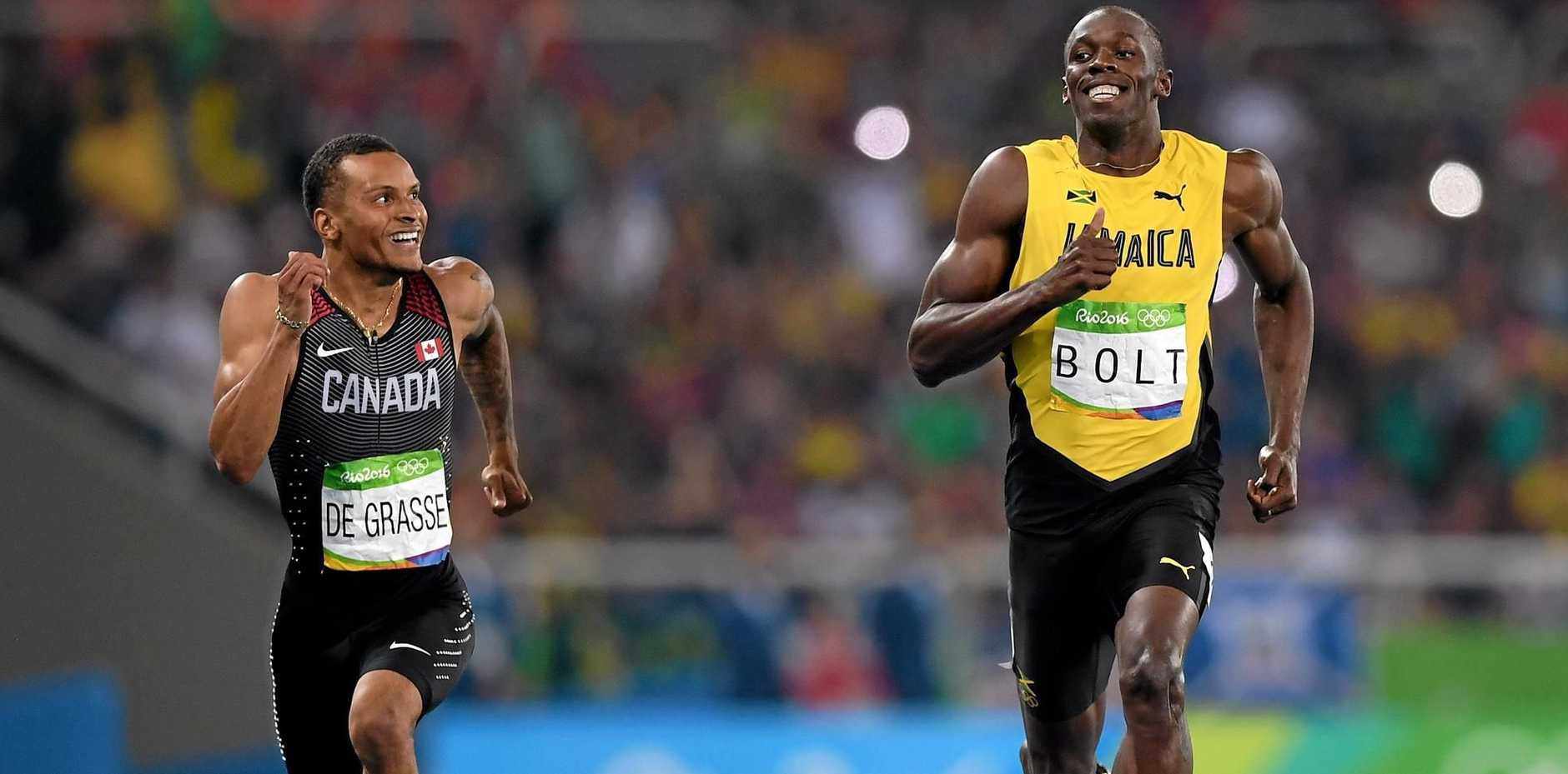 Andre de Grasse of Canada (L) and Usain Bolt of Jamaica react as they cross the line.