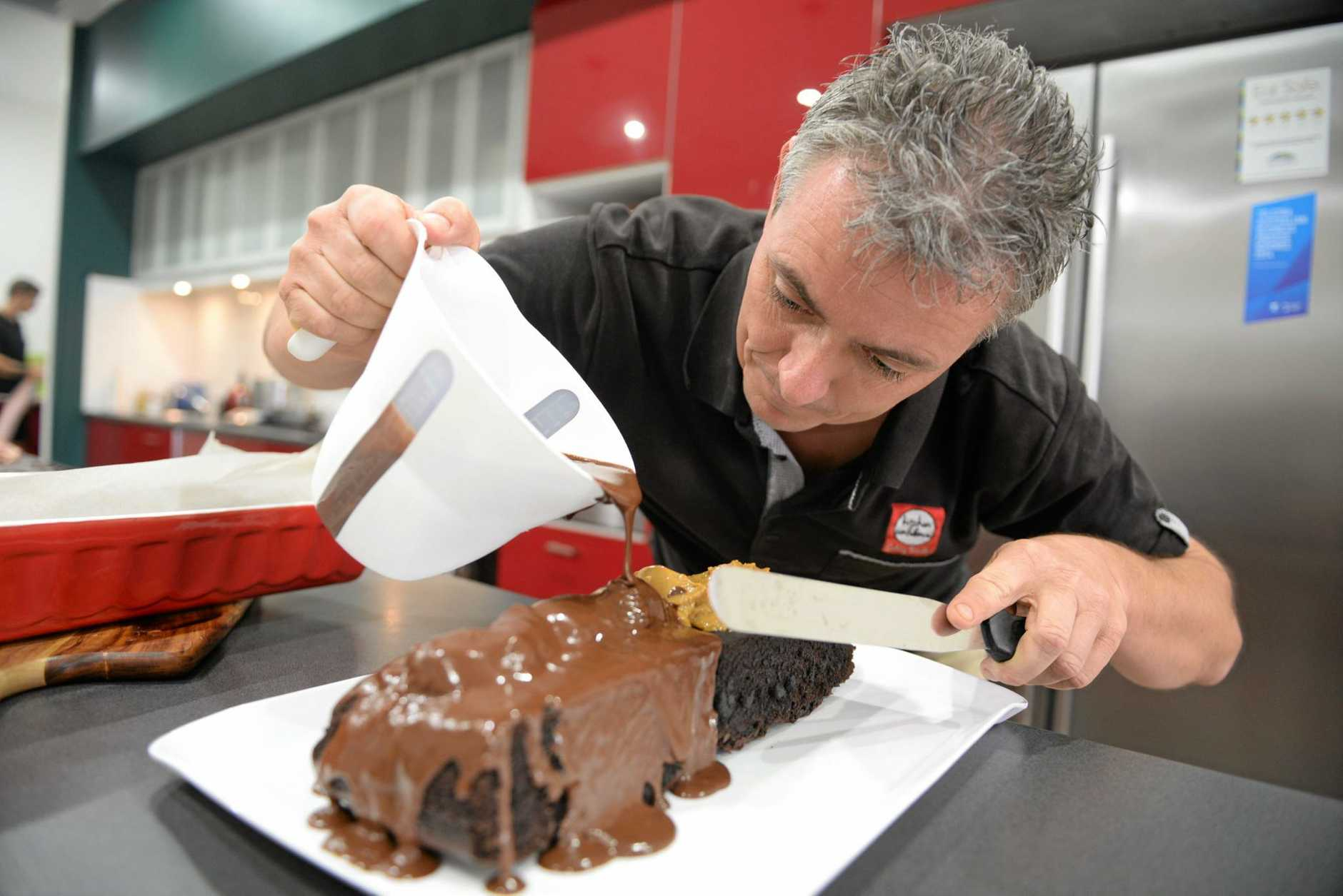 MOUTH WATERING: Wayne Bryans from Kitchen Confidence prepares a Chocolate Caramel Mud Cake. Photo: Max Fleet / NewsMail