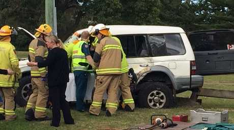 Emergency services work to free a woman from a 4WD that collided with a concrete truck.