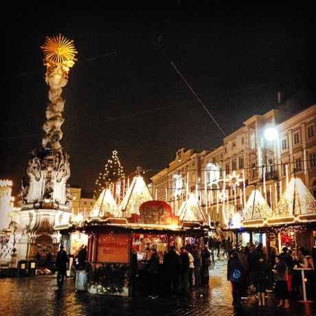 Linz's Christmas Market in the Main Square is brightly lit.