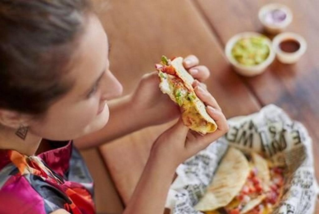 A customer enjoys her soft taco at Guzman y Gomez.