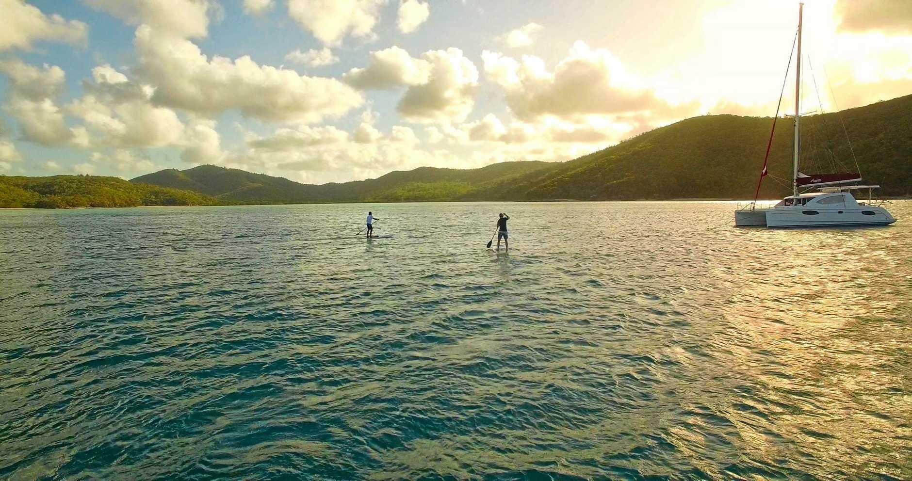 Hayden Quinn and Dan Churchill standup paddleboarding in the Whitsundays.