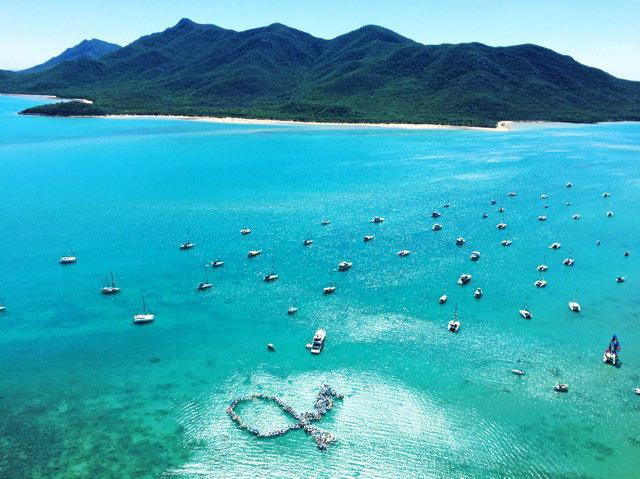 RAISING AWARENESS: 156 dinghies formed the shape of the ribbon used as a logo for the Prostate Cancer Foundation of Australia at the annual SICYC. Photo Sharon Smallwood / Whitsunday Times.