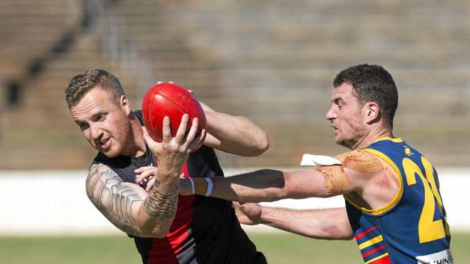 CONTEST: South Toowoomba's Scott McLeod tries to evade University's Rick Mackay in the AFL Darling Downs major semi-final at Heritage Oval.