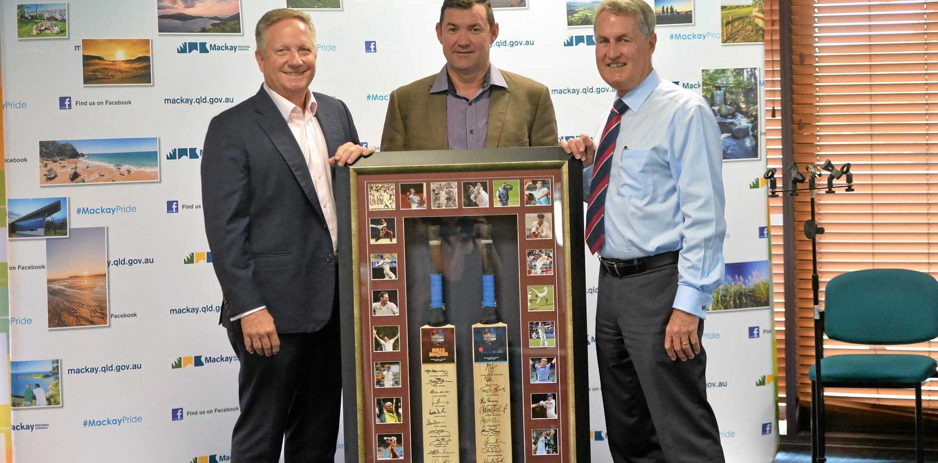 Australian cricketers Ian Healy and Jimmy Maher present Mayor Greg Williamson with the framed bats signed by the Baggy Blues and Bulls Masters teams. The bats are taking pride of place in the mayor's office.