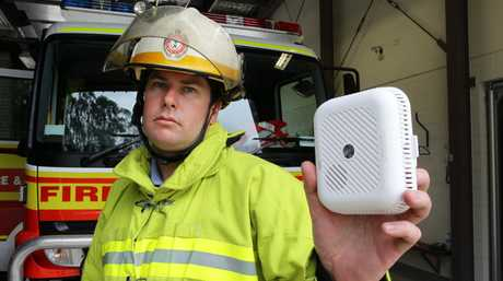 Senior fire fighter Glenn Urquhart holds the photoelectric smoke alarm which is the preferred type to replace the older model. Photo Barry Leddicoat / Sunshine Coast Daily