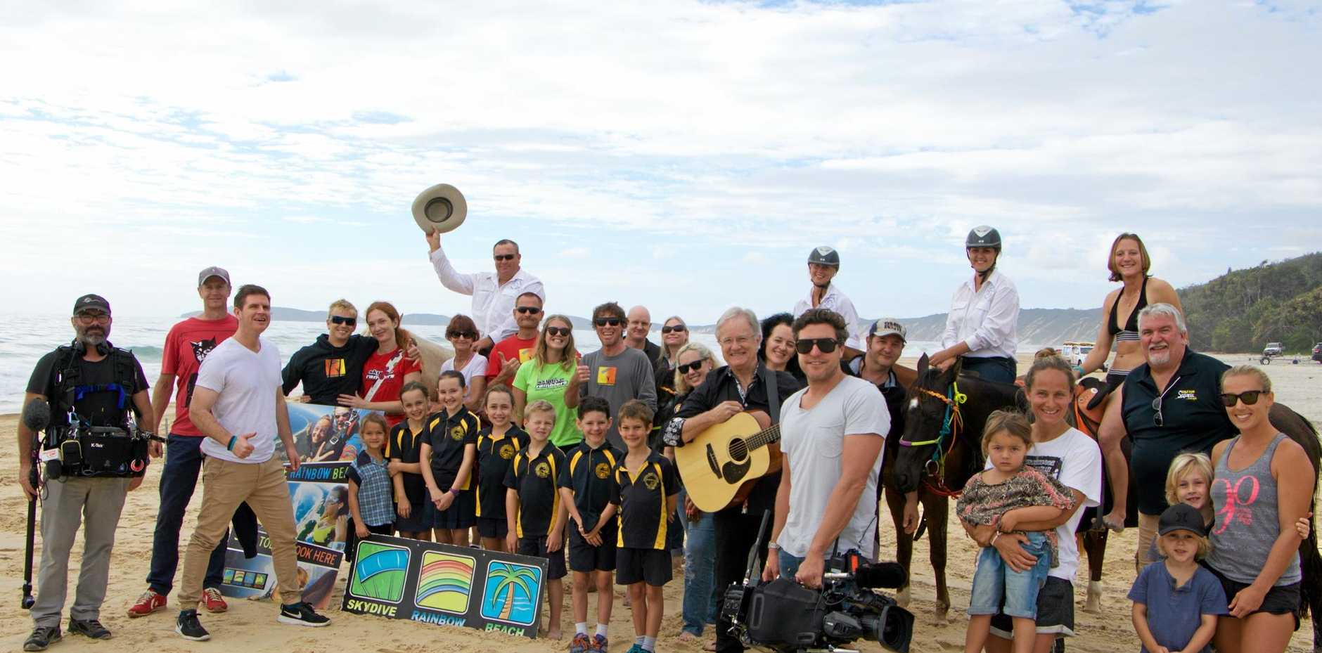 GOOD MORNING: Rainbow Beach locals greet Sam McMillan (Third from left) and the 'Sunrise' crew yesterday.