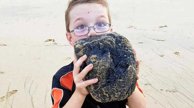Madalyn Barret's son with the large chunk of coal they discovered at East Point on Wednesday.