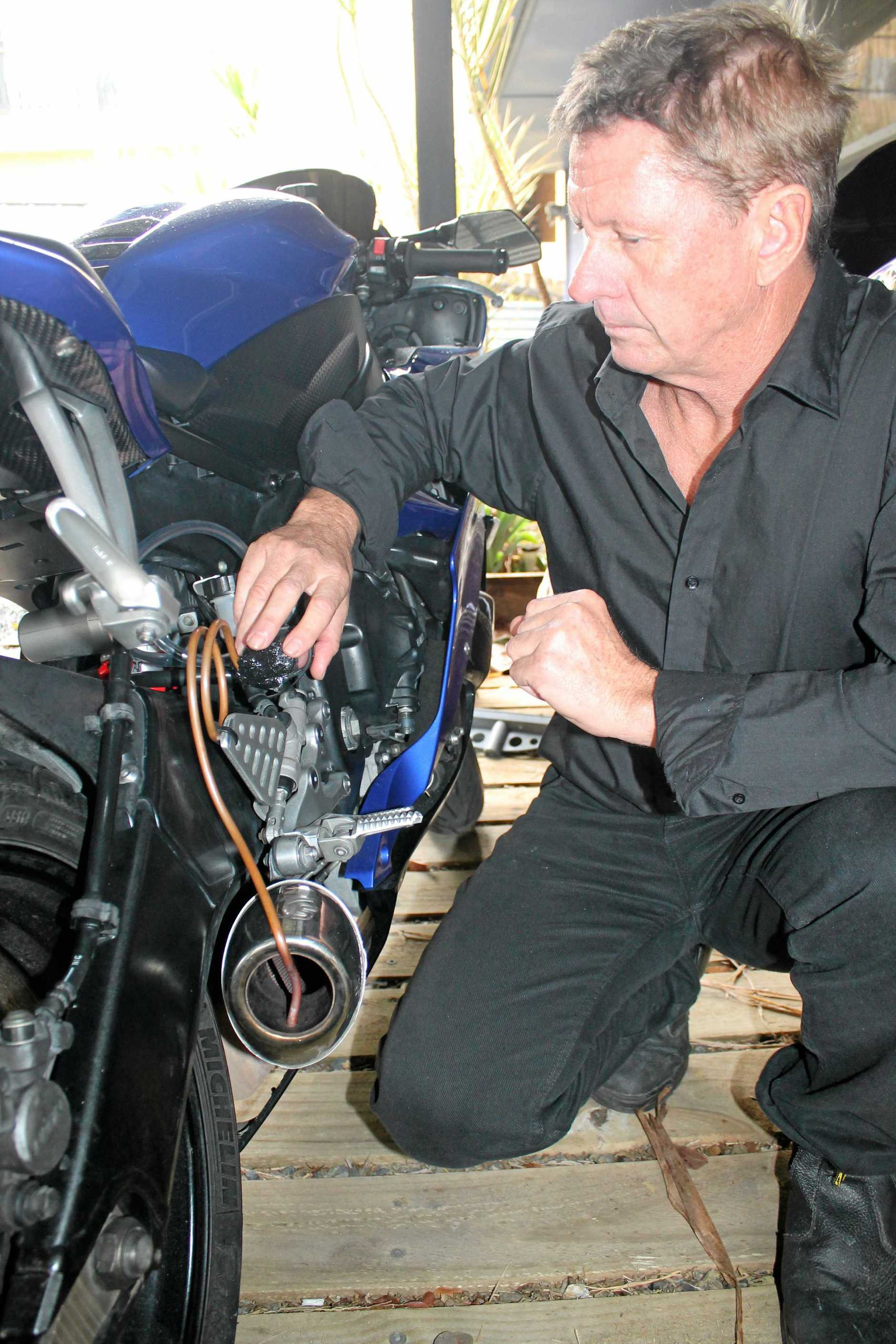 POTENTIAL FUEL SAVER: East Ballina inventor Brett Head with his Vapour Draw Systems fitted to a motorcycle.