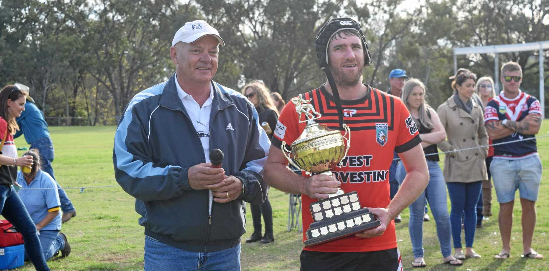 Border Rugby League president Norm Crisp presents the premiership trophy to Inglewood Roosters captain-coach Brent Osborne.