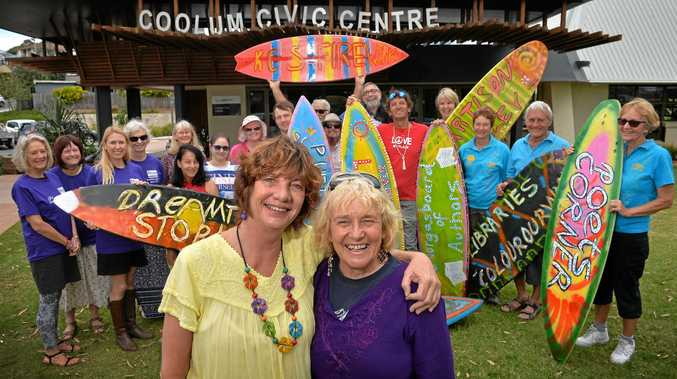 Wendy O'Hanlon and Eileen Walder with committee members and volunteers of the Sunshine Coast International Readers and Writers Festival show off their festival's funky surfboard signs in preparation for the festival.