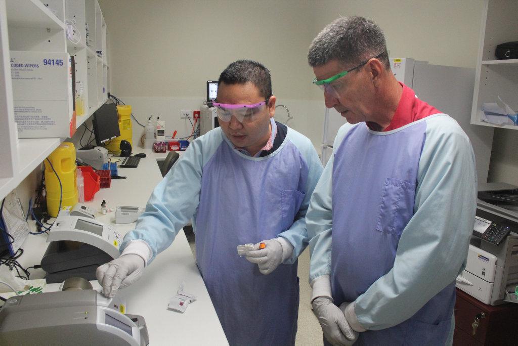 TEST: Pathology lab staff member Ed Duarte showed Maryborough MP Bruce Saunders around the new lab when it opened.