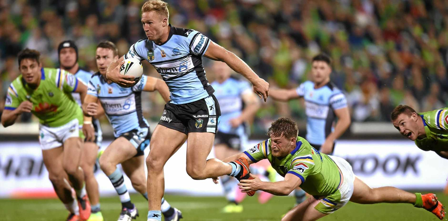 Matt Prior of the Sharks gets past a tackle by Elliot Whitehead of the Raiders during their NRL qualifying final.