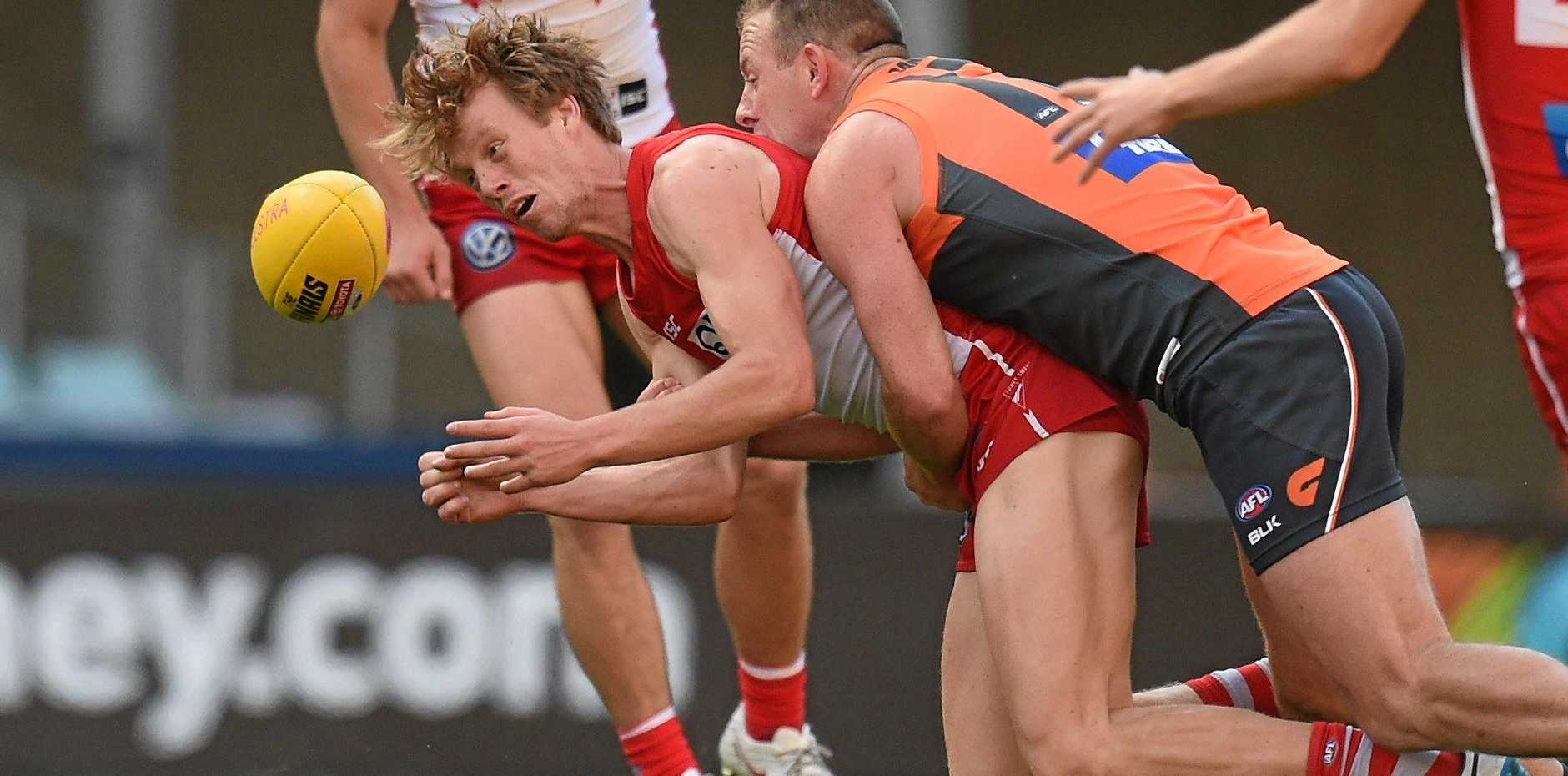 Callum Mills of the Swans losses possession with this tackle from Steve Johnson of the Giants during the first qualifying final.