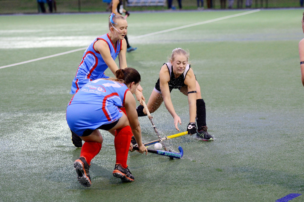 Swifts and Wests A-Grade players battle hard in the wet conditions on Saturday night before the field dried out.