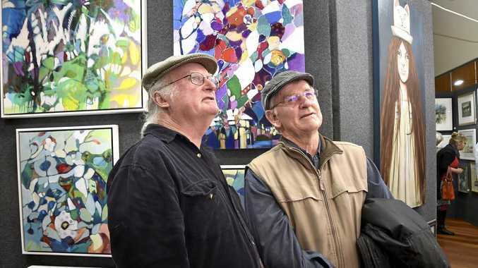 David Keim (left) and Darell Bishop discuss some pieces in the Downlands Art Exhibition Downlands Art Show. September 10, 2016