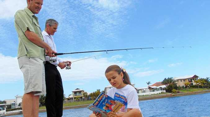 BETWEEN LINES: Fishing guru Rob Paxevanos and Sunshine Coast division two councillor Tim Dwyer listen up as Hailey reads some tips from Kids Fishing, the book she and her dad have written.