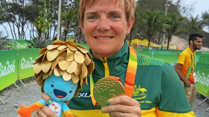 BACKED UP: Carol Cooke proudly displays her gold medal for the 15km T2 time trial in Rio.