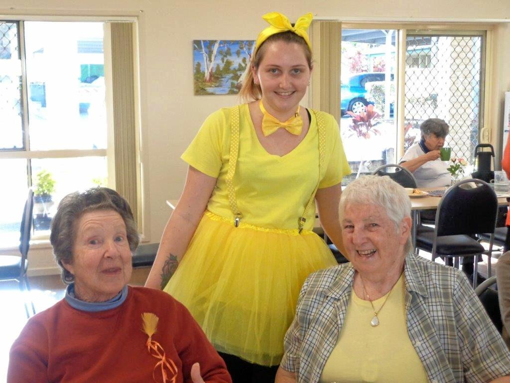 RUOK DAY: Cook Alicia Nye, dressed as a yellow fairy (standing), with Fay Mueck and Lola Miller (seated).