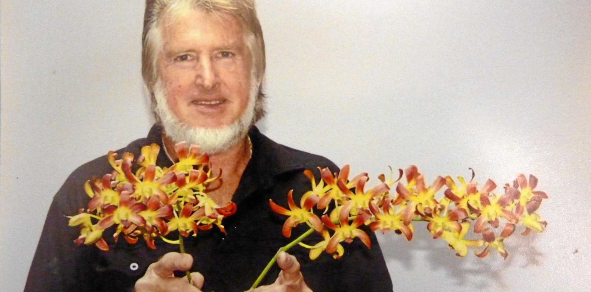 Woolgoolga District Orchid Society President Brian Newman with an award winning Dendrobium orchid, C.K. Ai 'Oka'
