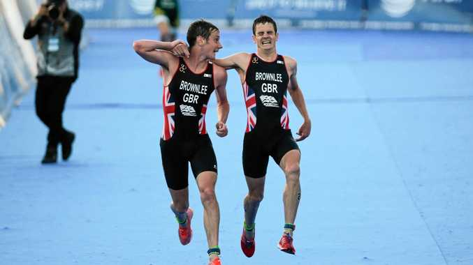 Alistair Brownlee (left) of Britain helps his brother Jonny to reach the finish line in the 2016 ITU World Triathlon event in Cozumel, Mexico.