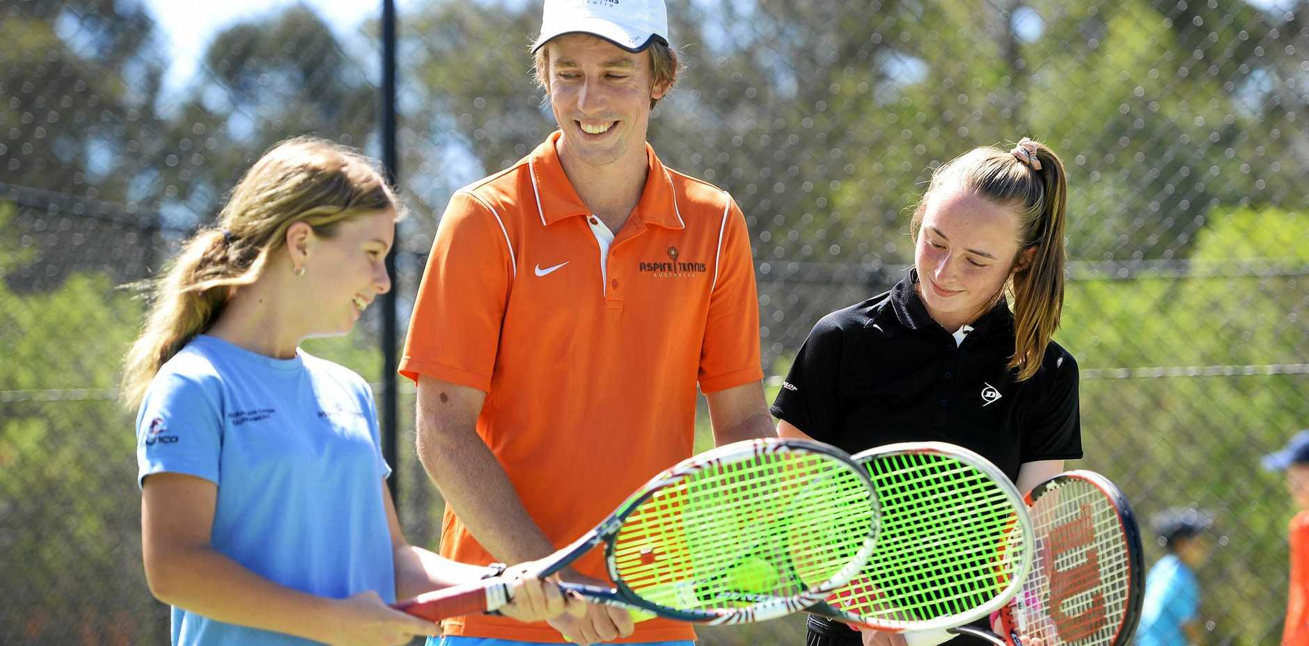 FUN LEARNING: Tennis coach Mitch Garen gives some advice to tennis players Sharni Higgins and Shontai Meloury at the Aspire Tennis Centre.
