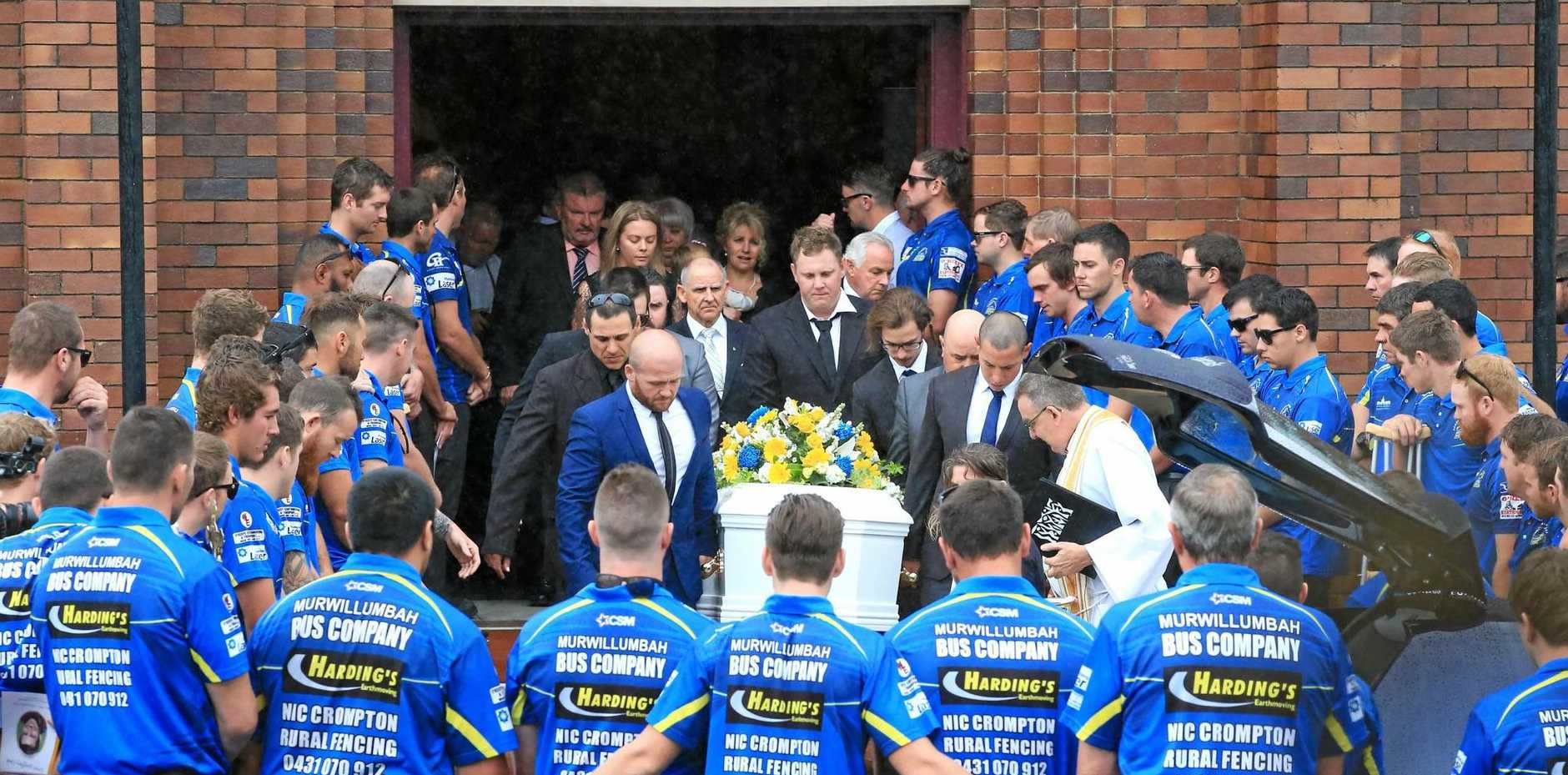 Mustangs players form a guard of honour as the coffin of Grant Cook is carried out of the church.