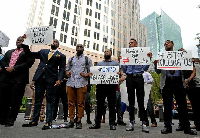 People gather at Trade and Tryon Streets in uptown Charlotte, N.C., in protest of a police officer's fatal shooting Tuesday of Keith Lamont Scott, Wednesday afternoon, Sept. 21, 2016. Scott was shot at The Village at College Downs apartment complex in the University City area. Authorities in Charlotte tried to quell public anger Wednesday after a police officer shot a black man, but a dusk prayer vigil turned into a second night of violence, with police firing tear gas at angry protesters and a man being critically wounded by gunfire.  (Jeff Siner/The Charlotte Observer via AP)