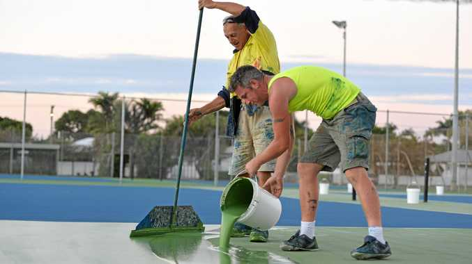 IN THE WORKS: Advantage Sports and Leisure's Greg Runnalls and Tommy Murphy (front) paint the surface of the Kippen St tennis courts.