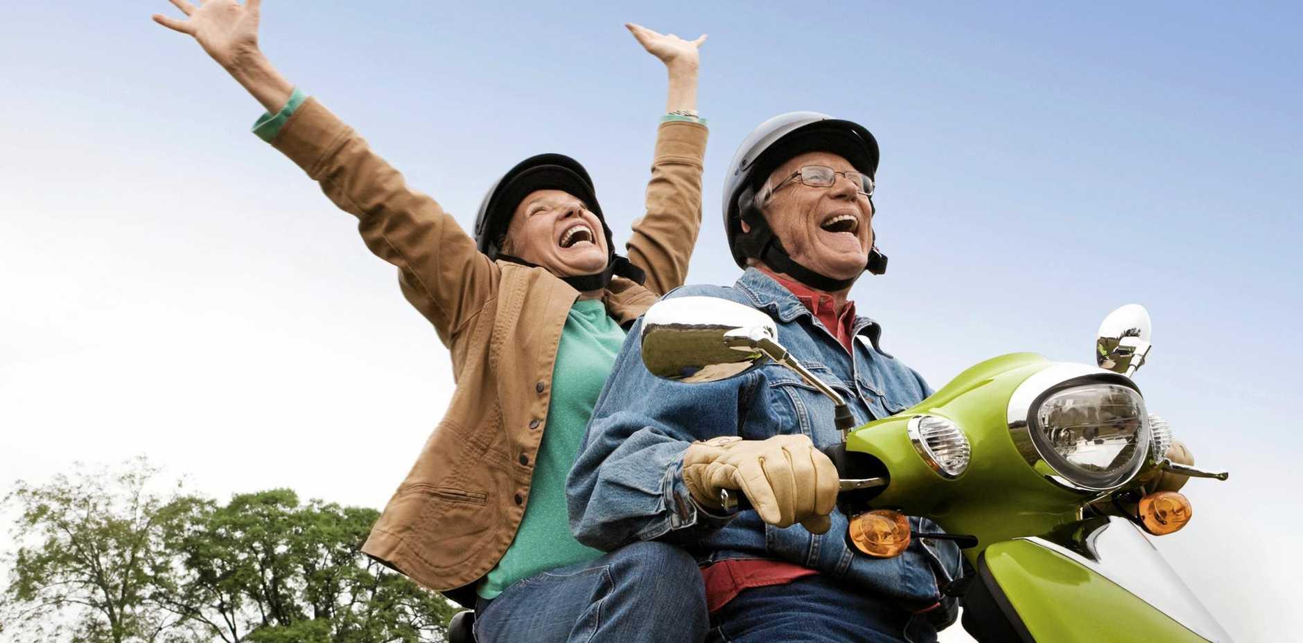 Senior couple riding motor scooter having fun.